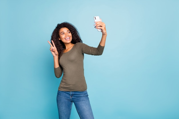 Portrait of positive cheerful wavy hair afro american girl blogger influencer have weekend journey take selfie on mobile phone make v-sign wear green sweater denim jeans isolated blue color wall