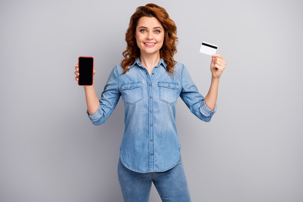 Portrait of positive cheerful woman promoter hold smartphone recommend online banking payment service system wear style stylish trendy outfit isolated over grey color wall