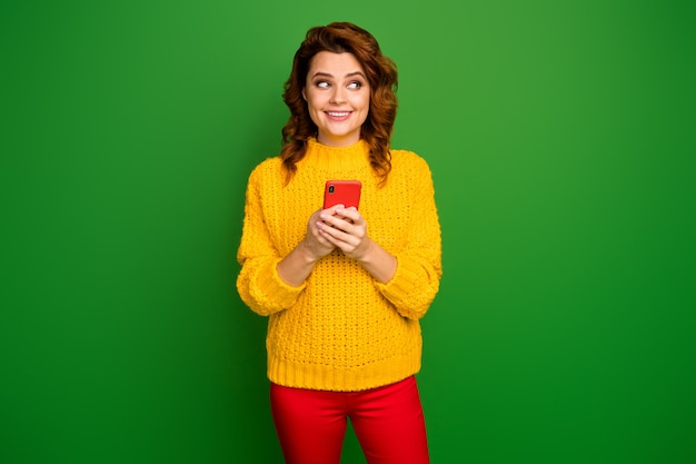 Portrait of positive cheerful woman use cellphone look copyspace post social network feedback wear knitted style stylish trendy sweater isolated over bright shine color wall