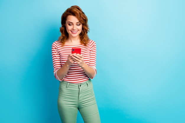 Portrait of positive cheerful woman use smartphone read social media news information wear stylish jumper isolated over blue color