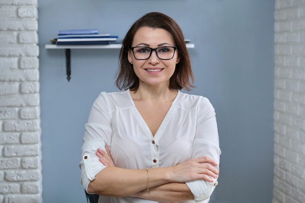 Portrait of positive confident middle aged woman with arms crossed, female teacher, counselor, tutor, coach working in office, smiling looking at camera