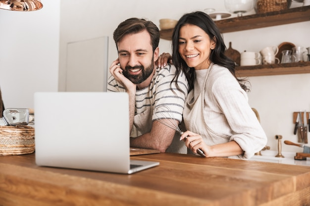 Portrait of positive couple man and woman 30s wearing aprons looking at laptop while cooking pastry in kitchen at home