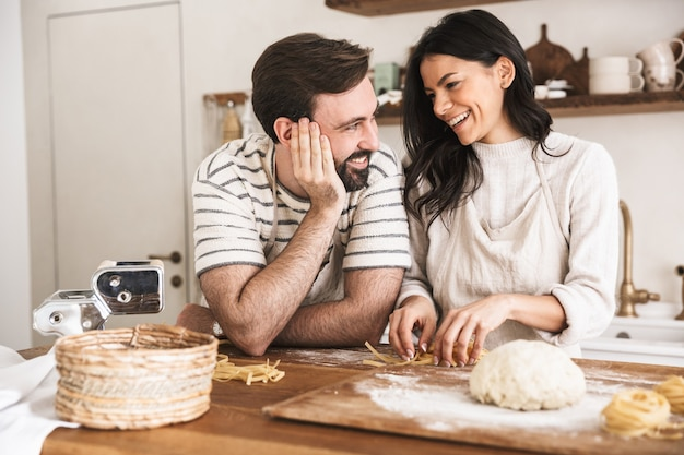 Portrait of positive couple man and woman 30s wearing aprons making homemade pasta of dough while cooking together in kitchen at home