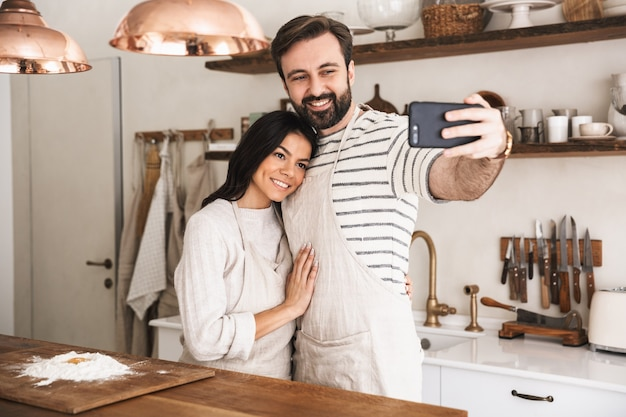 Portrait of positive couple man and woman 30s wearing aprons taking selfie photo while cooking pastry with flour and eggs in kitchen at home