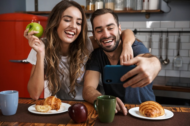Portrait of positive couple man and woman taking selfie photo on cell phone while having breakfast in kitchen at home