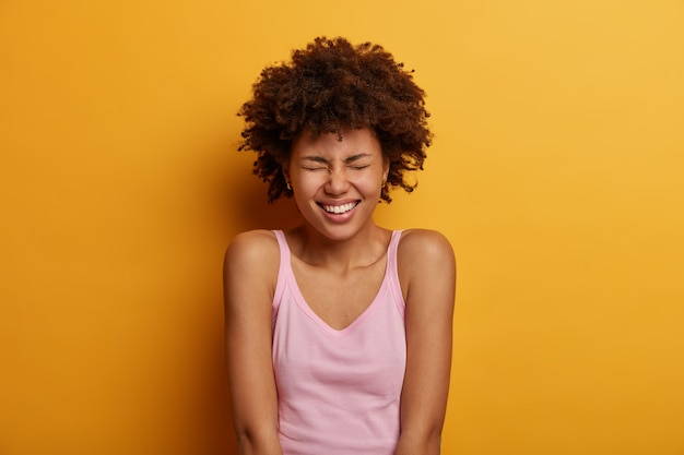 Portrait of positive ethnic woman squints face, smiles happily, shows white teeth, being in high spirit, enjoys day off, listens good jokes from friend, wears casual vest, models against yellow wall