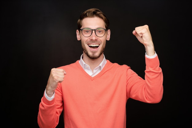 Portrait of positive excited young bearded man in glasses making yes gesture against black background