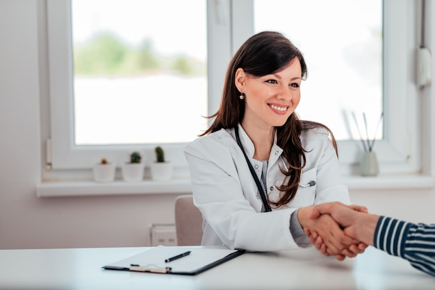 Portrait of a positive female doctor greeting with a patient.