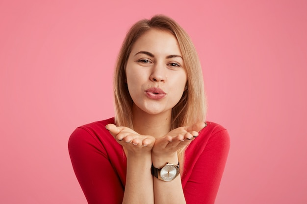 Portrait of positive female wears red sweater and trendy watch, blows kiss as flirts with someone, expresses love and good feelings, isolated over pink wall. glamour woman makes kiss.