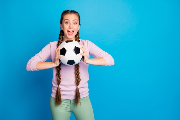 Portrait of positive funny youth girl feel enthusiastic hold foot ball want throw support her team on final championship game wear modern outfit isolated over bright color background
