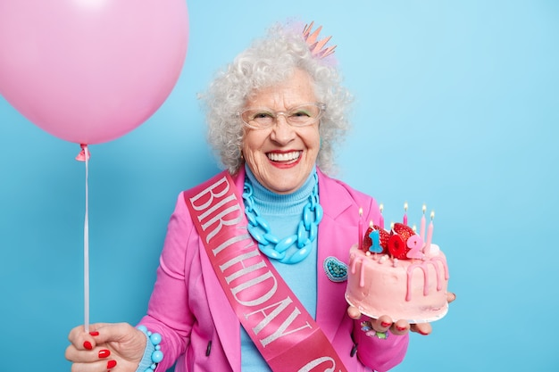 Portrait of positive grey haired woman celebrates 102nd birthday, holds tasty cake and inflated balloon