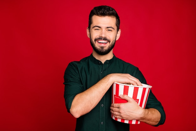 Portrait of positive guy have break pause watch funny movie hold big red striped pop corn box enjoy recreation wear casual style clothes
