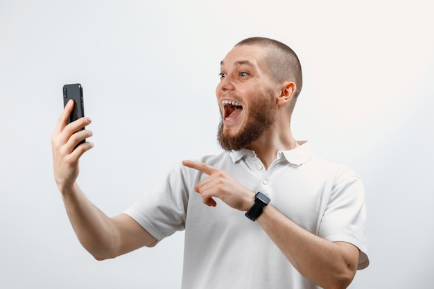 Portrait of a positive handsome bearded man in a white t-shirt talking on video call using a smartphone
