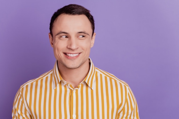 Portrait of positive handsome guy look side empty space shiny white smile on violet background