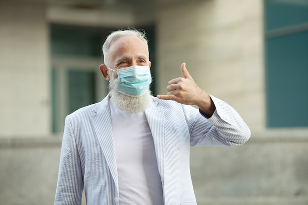 Portrait of positive handsome senior business man with medical mask smiling friendly and waving hand