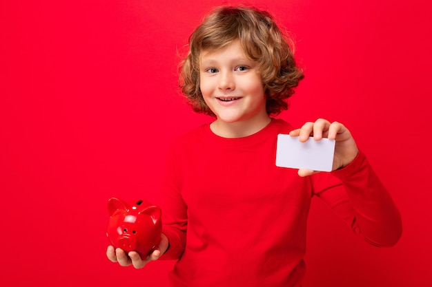 Portrait of positive happy smiling little boy with curly blond hair with sincere emotions wearing casual red pullover isolated over red background with copy space, holds red piggy box for coins and cr
