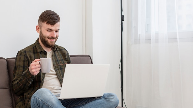Portrait of positive male enjoying work from home