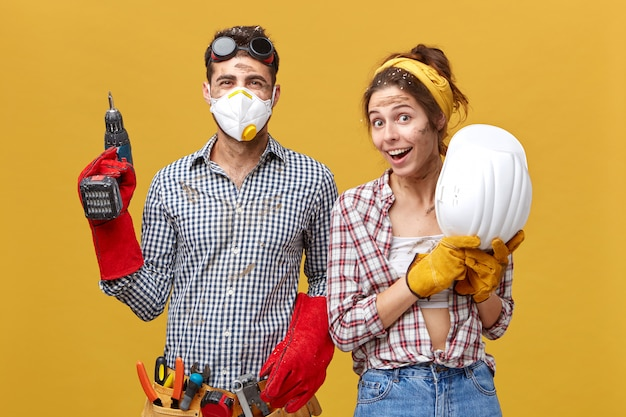 Portrait of positive male with drilling machine and tool belt and his female colleague holding hardhat having delightful expression