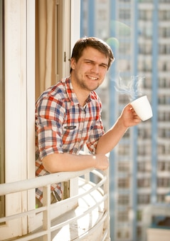 Portrait of positive man drinking coffee on balcony at morning