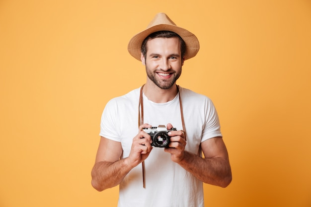 Portrait of positive man with retro camera standing isolated