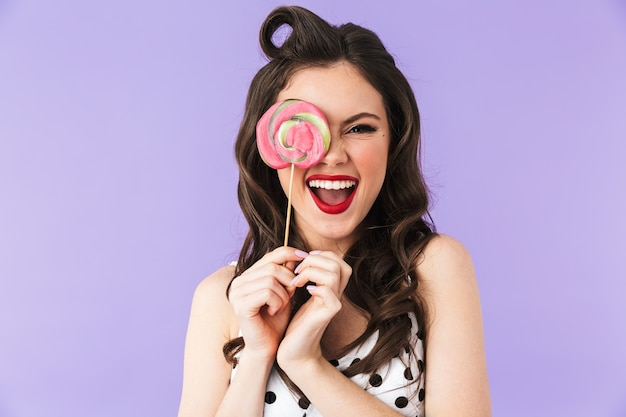 Portrait of positive pin-up woman in vintage polka dot dress smiling while holding and eating colorful lollipop isolated over violet wall