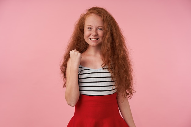 Portrait of positive redhead female teenager with long curly hair raising hand in yes gesture, looking joyfully to camera and showing her white teeth, isolated over pink background