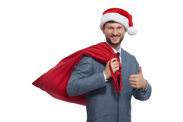 Portrait of positive santa claus in gray suite, red cap and full bag over shoulder, smiling and showing super.