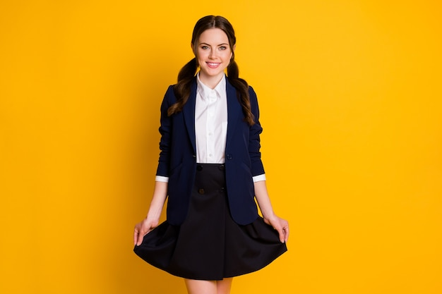 Portrait of positive school student touch her skirt posing