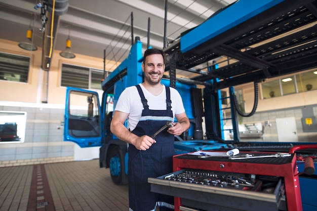 Portrait of positive smiling truck serviceman with tools standing by truck vehicle in workshop
