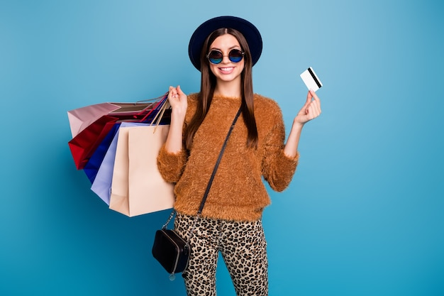 Portrait of positive tourist girl money payer walk autumn winter shop mall retail hold credit card wear brown sweater trousers sunglass velvet retro vintage cap isolated blue color wall