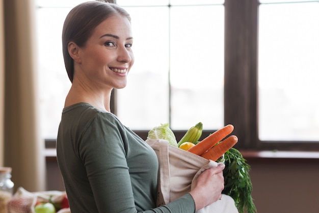 Portrait of positive woman holding bag with fresh groceries