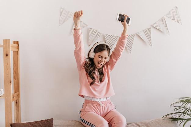 Portrait of positive woman in pink sweatshirt joyfully raising hands up
