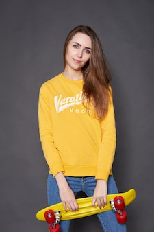 Portrait of positive young attractive girl wearing yellow blouse and blue jeans holding yellow skateboard.