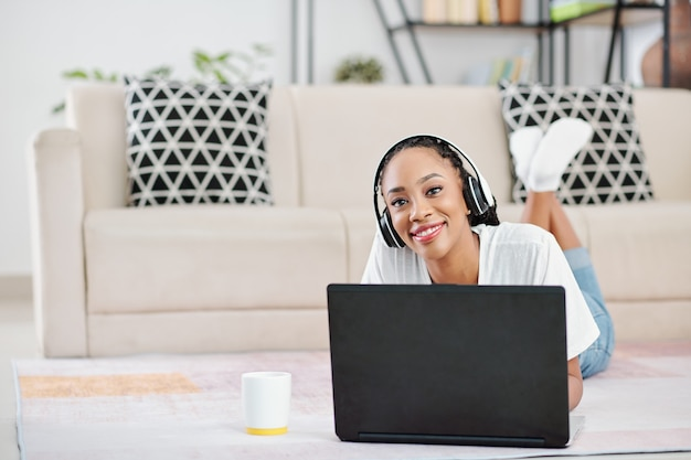 Portrait of positive young black woman wearing headphones when lying on the floor and working on laptop at home