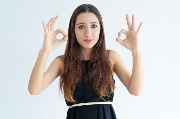 Portrait of positive young businesswoman showing ok sign