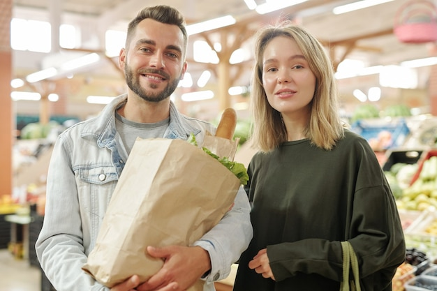 Portrait of positive young couple standing at farmers market and purchasing organic food together