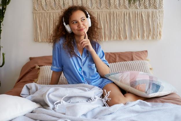 Ritratto di positiva giovane ragazza mulatta riccia sdraiata a letto, vestita in pigiama blu, sorridente e godersi la sua canzone preferita in cuffia, distoglie lo sguardo sognante e tocca il mento.