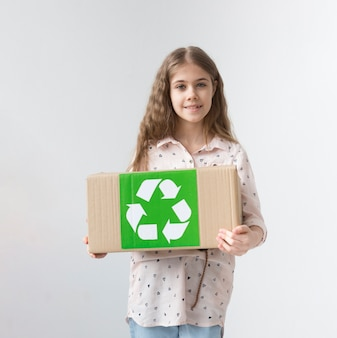 Portrait of positive young girl holding recycling box
