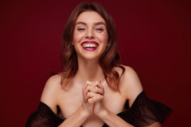 Ritratto di positiva giovane bella donna dai capelli castani vestita in abiti festivi guardando felicemente la fotocamera e sorridente ampiamente, attraversando le braccia alzate mentre in piedi su sfondo bordeaux