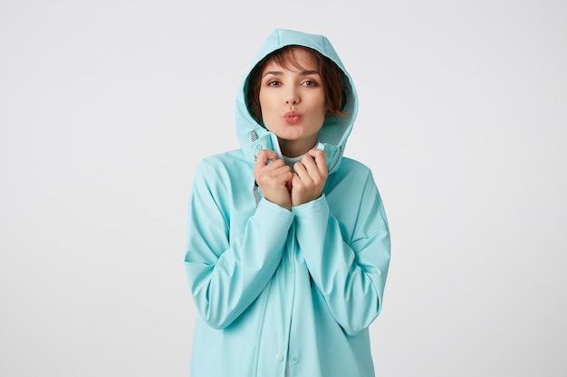 Ritratto di giovane bella signora positiva in cappotto di pioggia blu, con un cappuccio in testa, guarda la telecamera con espressioni felici, invia un bacio alla telecamera, si trova sopra il muro bianco.