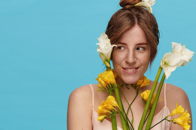 Portrait of positive young pretty lady with casual hairstyle wearing her foxy hair in knot while posing over blue background with bunch of yellow and white flowers