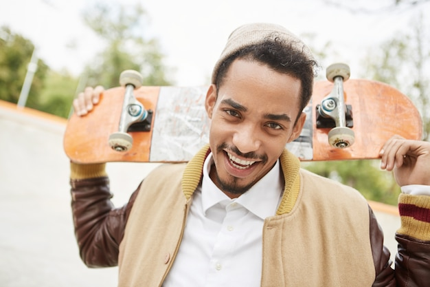 Portrait of positive young teenager practices riding skateboard outdoors, has happy expression