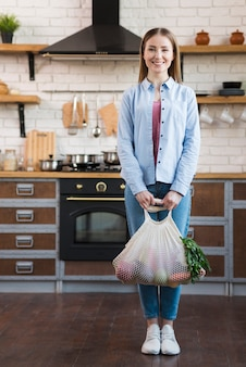 Portrait of positive young woman holding organic vegetables