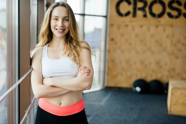 Portrait of positivity and girl smiling at camera and posing with crossed arms in the gym.