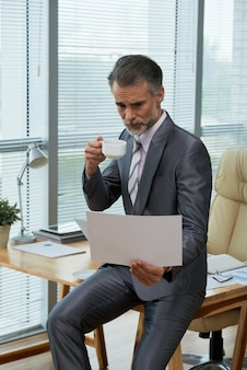 Portrait of powerful ceo perching on the desk browsing throught the report and sipping coffee