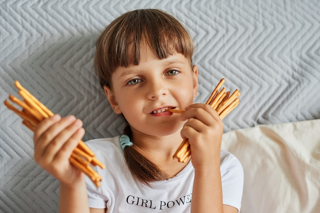 Portrait of preschooler female kid with dark hair and pigtails wearing white casual style t shirt holding in hands and biting pretzels sticks, looking at camera with satisfied facial expression.