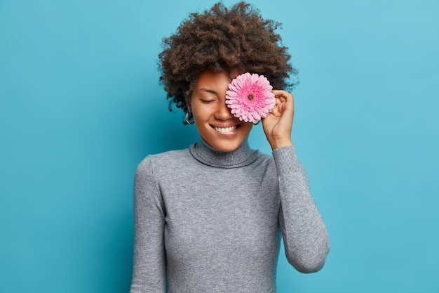Portrait of pretty afro american woman covers eye with rosy gerbera daisy, bites lips, smiles positively, likes flowers, wears casual turtleneck