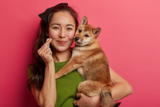 Portrait of pretty asian woman shows mini heart hand gesture, expresses love, embraces japanese pedigree hunting dog, enjoys spending free time with favorite pet