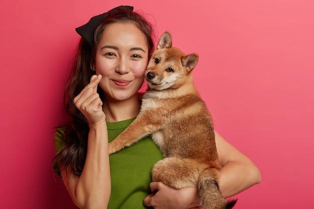 Ritratto di donna abbastanza asiatica mostra il gesto della mano mini cuore, esprime amore, abbraccia cane da caccia di razza giapponese, ama trascorrere il tempo libero con l'animale domestico preferito
