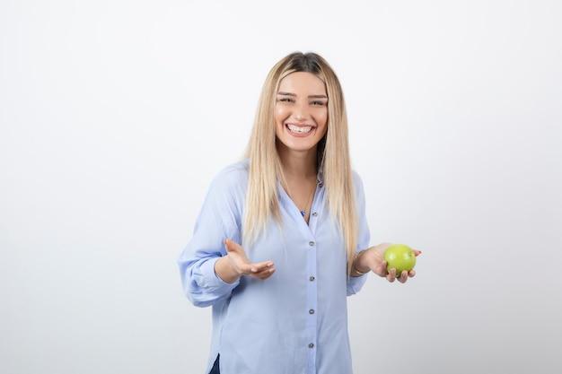 Ritratto di un modello di donna piuttosto attraente in piedi e in possesso di una mela fresca verde.